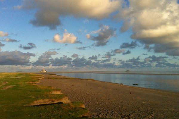 Entre le ciel, la terre et l'eau : le Mont Saint Michel émerge en toute majesté, lors des grandes marées.