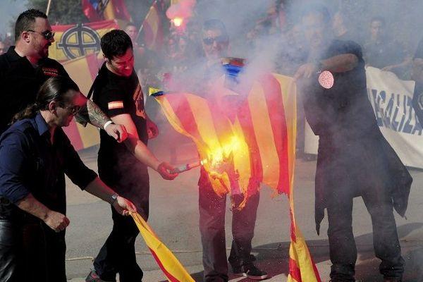Des militants anti-indépendantistes ont brûlé le drapeau catalan pendant la manifestation.Barcelone le 12 octobre 2014.
