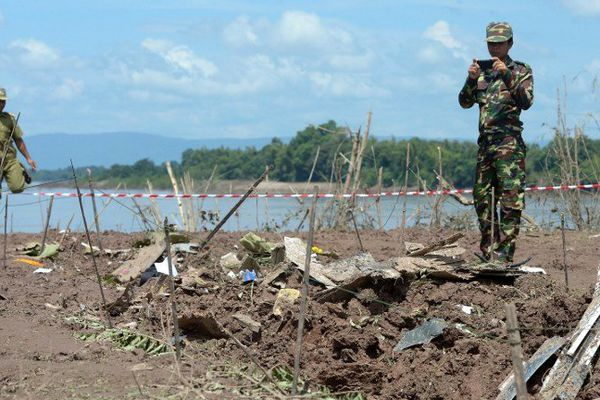 Un soldat laotien vieille sur quelques débris de l'avion qui s'est crashé le 16 octobre dans le Mékong.