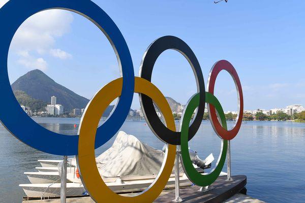 Les anneaux olympiques devant le plan d'eau où auront lieu les épreuves d'aviron