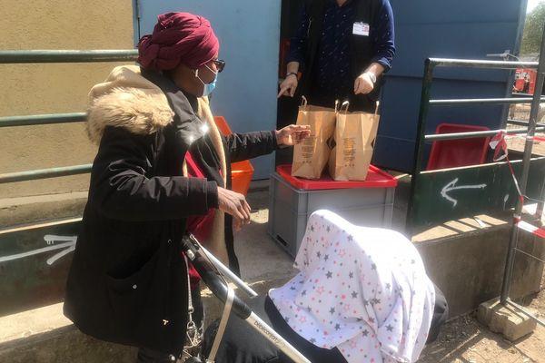Point de collecte au Relais Orléanais rue du Faubourg Madeleine, une femme avec une poussette vient récupérer de quoi manger.