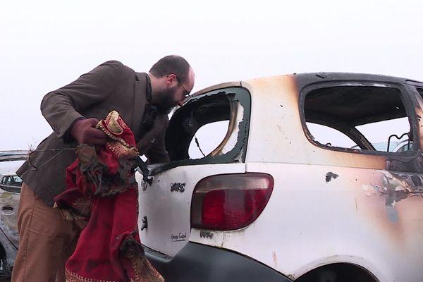 Florent Jacob devant l'épave calcinée de sa voiture