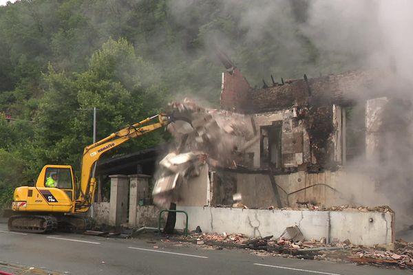 Une pelleteuse détruit ce qui reste de la maison pour éviter qu'elle ne s'écroule sur la route