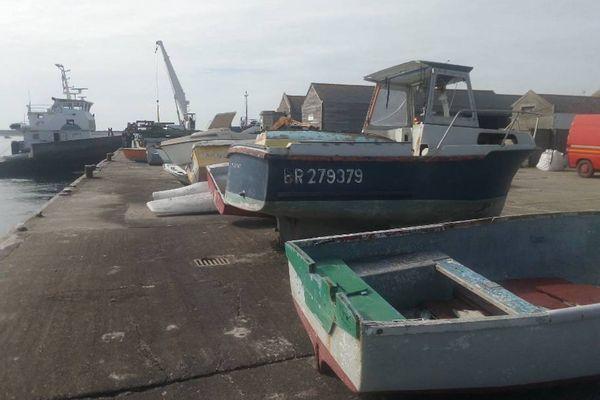 Sur le terre-plein du port de l'île de Sein, des épaves de bateau attendent d'embarquer pour leur dernier voyage.