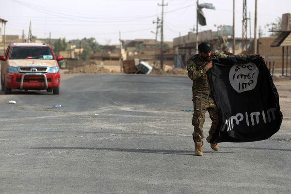 Un membre de Hashed al-Shaabi portant un drapeau de l'Etat islamique en Irak. (Illustration)