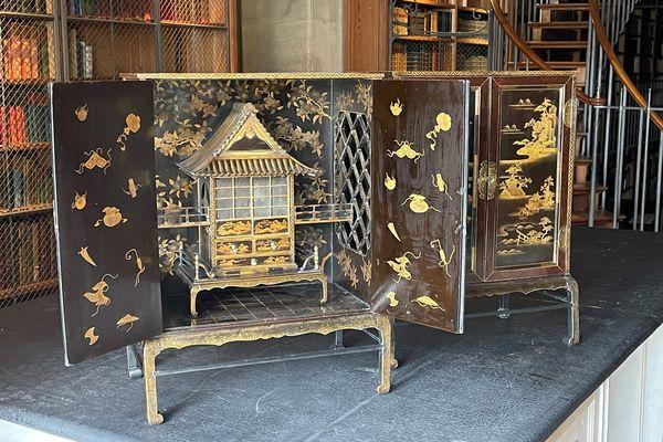 Cabinets en bois noir japonais avec incrustations de laque et des panneaux illustrés. À l'intérieur se trouve un temple miniature dotés de petits tiroirs.