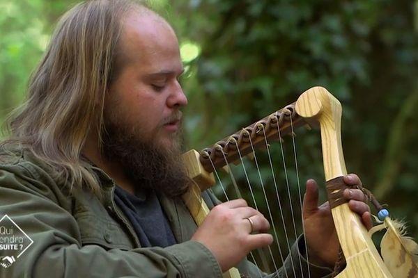 Julian Cuvilliez artisan, tient la lyre gauloise qu'il a reconstituée