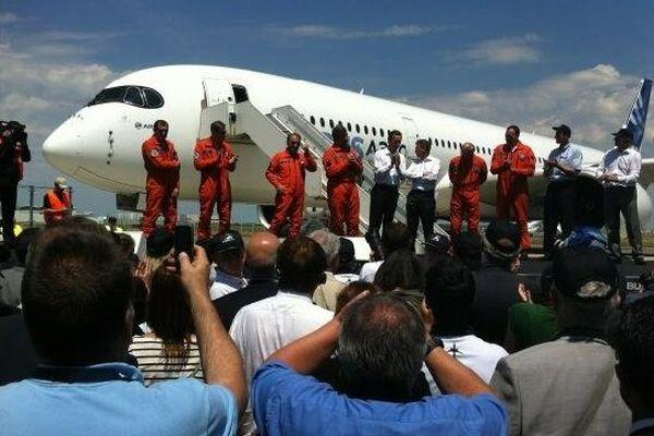 Les pilotes en rouge et l'équipe du programme sont accueillis par la foule des airbusiens