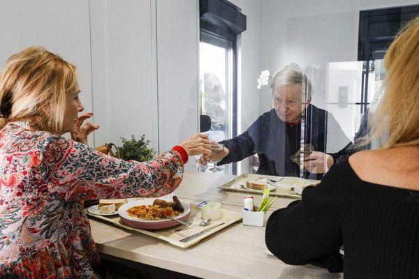 Un résident déjeune avec ses filles dans un mobile home à travers un écran en plastique dans un Ehpad.
