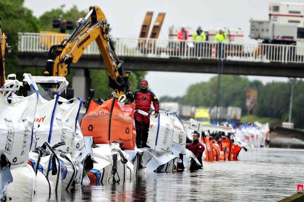 Au nord d'Orléans, une digue a été formée avec des sacs de sable pour pomper l'eau de la chaussée après les inondations de la fin du mois de mai.