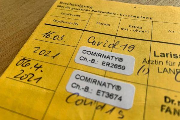 Un carnet de vaccination allemand, avec les deux doses du vaccin Comirnaty de Pfizer-Biontech