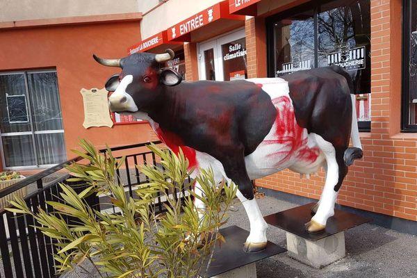 La vache qui vous accueille à l'entrée du restaurant a été barbouillée avec de la peinture rouge