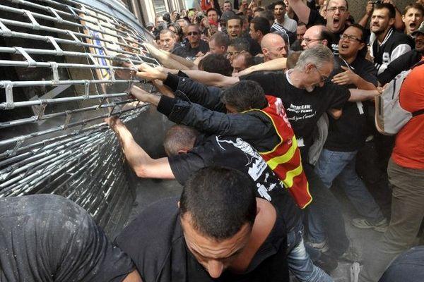 Mercredi 26 juin 2013. Des salariés de Michelin arrachent le rideau de fer qui protège l'entrée du siège social de la société à Clermont-Ferrand alors qu'un CCE extraordinaire se déroule à l'intérieur au sujet de la réorganisation de l'activité poids-lourds.