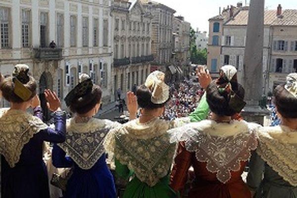 Camille Hoteman en costume vert salue la foule au balcon de la mairie accompagnée des demoiselles d'honneur