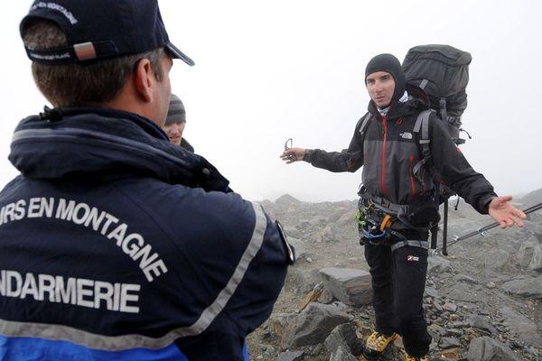 Photo d'illustration - Un gendarme du peloton de gendarmerie en haute montagne (PGHM) informe deux alpinistes que le campement sauvage sur le Mont-Blanc est interdit, près du refuge Tête Rousse à Saint-Gervais-les-Bains