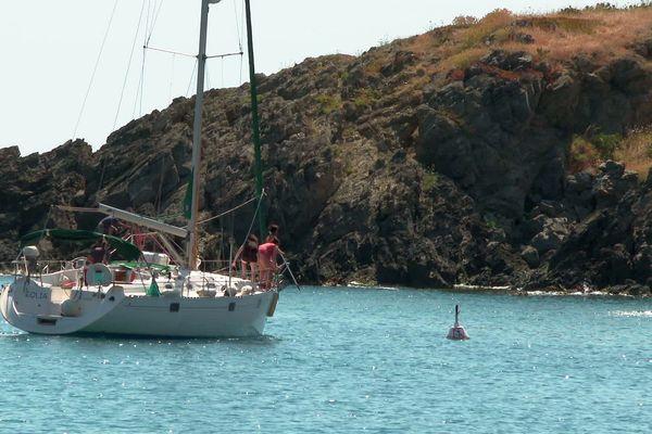 Un plaisancier en train de s'amarrer à une bouée écologique dans la baie de Peyrefite à proximité de Cerbère, en bordure de la Côte rocheuse des Pyrénées-Orientales. Grâce à ce système, son ancre n'abîmera pas la flore sous-marine.