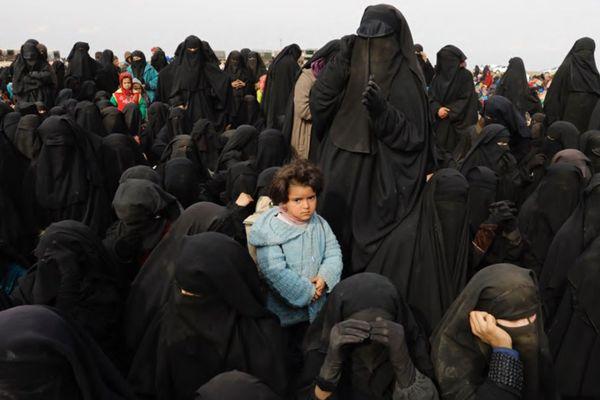 Syrie, 2019. Centre de tri de Tanak Field North. Des femmes et des enfants de djihadistes évacués de Baghouz attendent de recevoir des vivres, dans ce centre de tri improvisé dans le désert.
