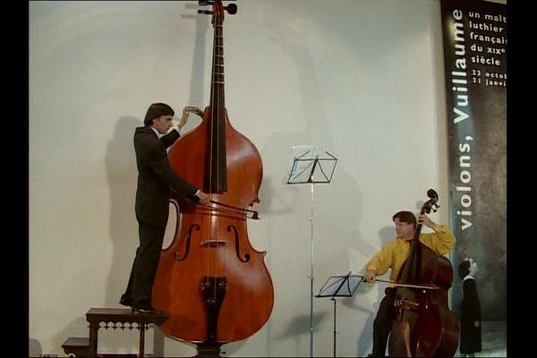 Musicien jouant de l'octobasse à côté d'une contrebasse.