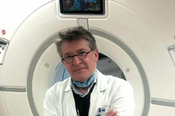 Pr Eric Delabrousse devant le scanner utilisé pour les examens du Covid-19