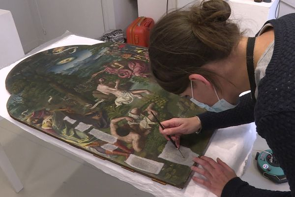 """Hélène Wallart, restauratrice d'art travaille sur cette huile sur bois """"Le baptême du Christ"""" au musée Sandelin de Saint-Omer"""