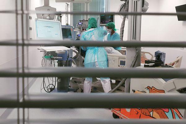 Des soignants s'affairent autour d'un patient afin de lui faire passer une radio, grâce à un appareil mobile, dans une chambre de réanimation de l'hôpital de Chambéry.
