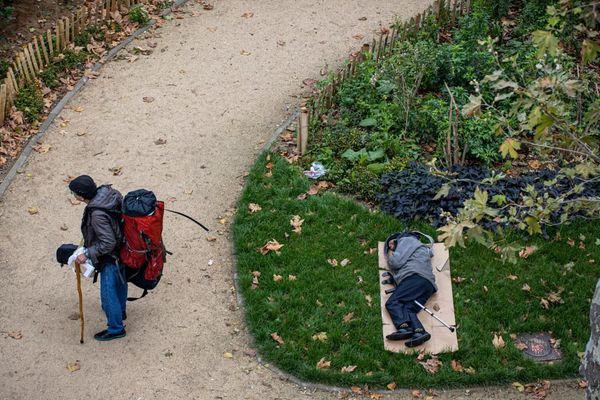Un SDF assoupi dans un parc près de la place de la Chapelle à Paris, début octobre.