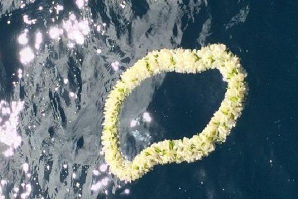 Une couronne de fleurs lancée à la mer comme un dernier cadeau offert à Laurent Bourgnon