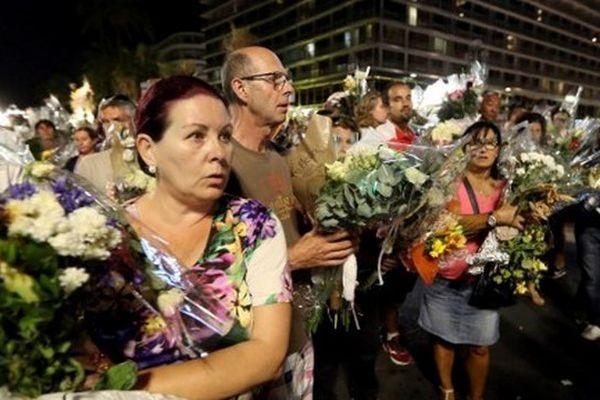 """Une chaîne humaine composée de centaines de personnes a déplacé dans l'émotion lundi soir les fleurs, peluches et mots d""""hommage."""