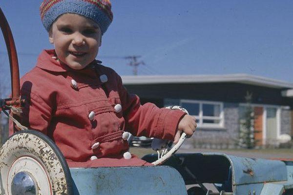 Jeune enfant portant un bonnet de laine et conduisant une voiture jouet - Gar Lunney - Avril 1961
