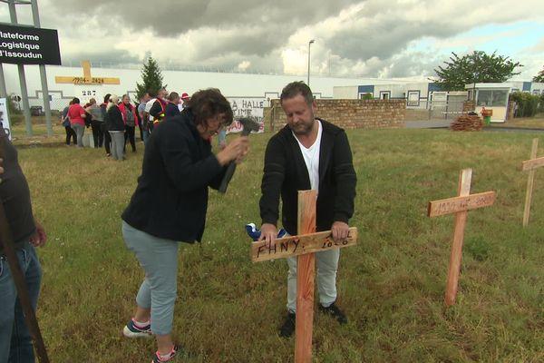 Brigitte plante une des croix qui symbolisent les emplois en sursis du dépôt logistique de la Halle à Issoudun dans l'Indre