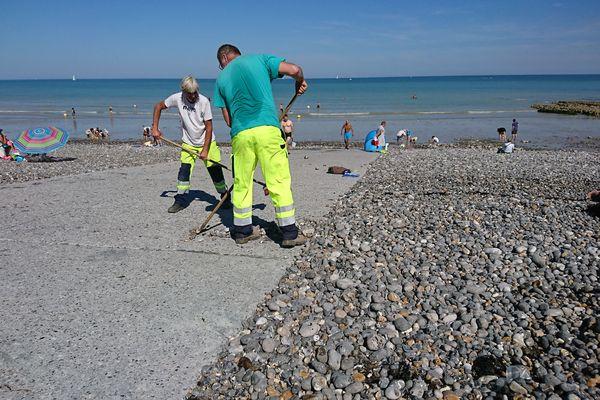 Les employés de la ville de Puys déblayent les galets de la digue