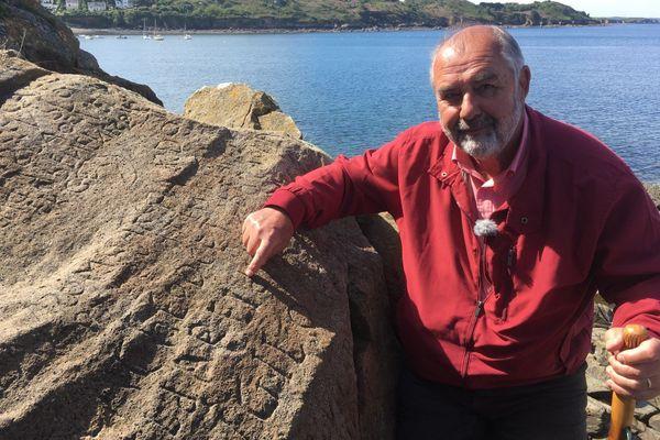 Stéphane Michel, conseiller municipal de Plougastel-Daoulas devant le rocher et ses inscriptions mystérieuses