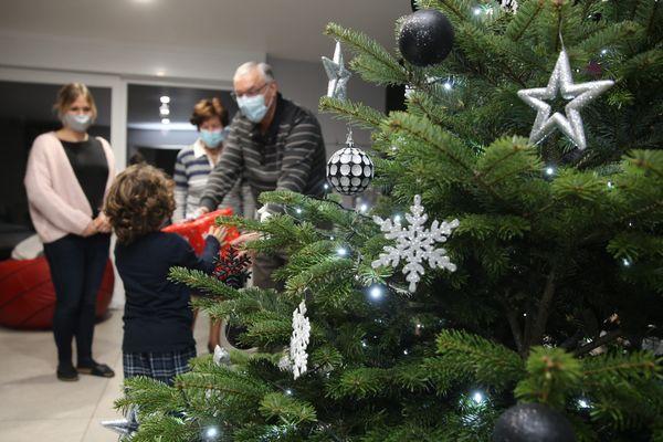 Une famille avec masque contre le Coronavirus lors de la distribution de cadeaux au pied du Sapin de Noël.
