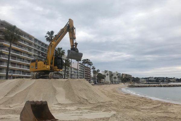 28 avril 2021 - Juan-les-Pins (Alpes-Maritimes) : le sable a été livré sur la plage, il est ensuite étalé par les agents municipaux à l'aide d'une pelleteuse.