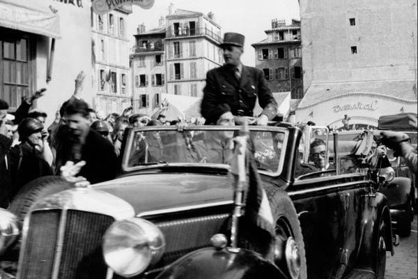 Le général de Gaulle est salué par la foule durant sa traversée de Nice en voiture, le 14 septembre 1948.