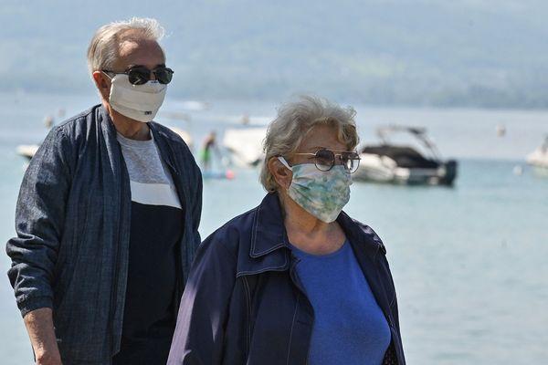 - Photo d'illustration - Deux personnes portant des masques de protection marchent le long des rives du lac d'Annecy le 17 mai 2020.