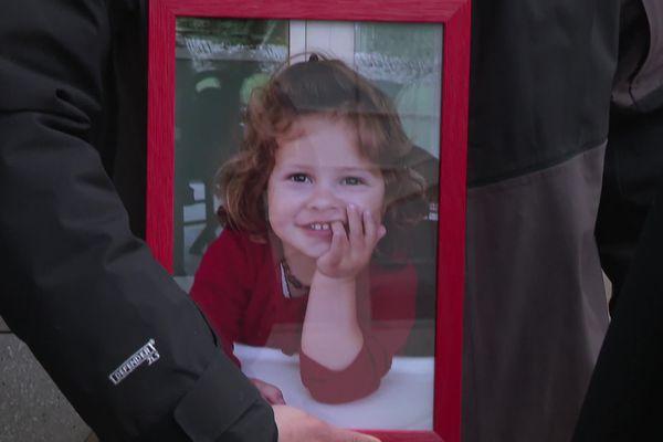 Son père porte contre lui la photo de l'enfant. La petite fille a trouvé la mort en juin 2017.