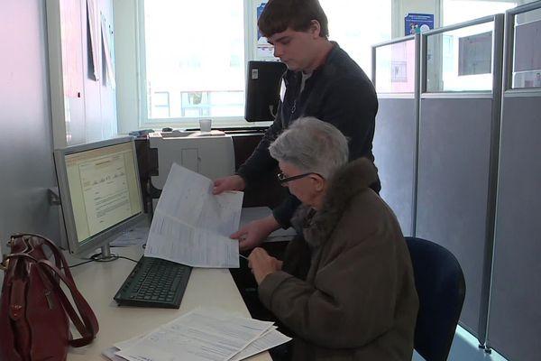 Un contribuable fait sa déclaration en ligne au centre des impôts de Dieppe, accompagné par un jeune en service civique