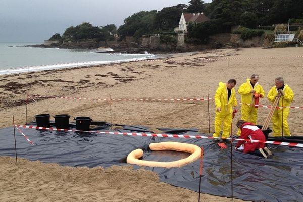 Mise en place d'une aire de décontamination sur la plage juste après l'arrivée supposée de la pollution