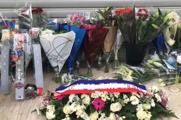 Des fleurs déposées devant la boutique, en hommage au jeune homme décédé.