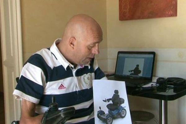 Philippe Croizon montrant l'image du fauteuil qui lui a été volé