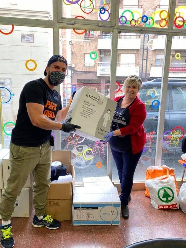 La Présidente de l'Association Catalane + Tú distribuant du matériel confectionné par les bénévoles.