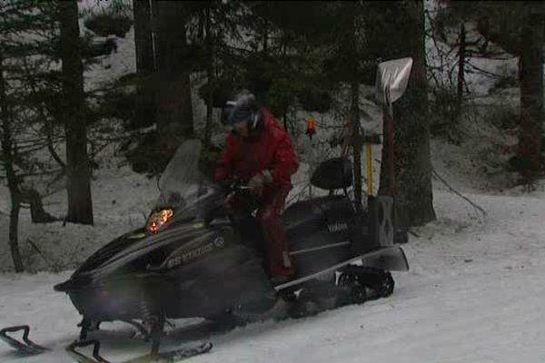 En moto-neige pour entretenir le parcours de ski nordique.