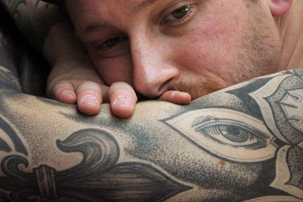 Un homme se fait tatouer au Mondial du tatouage, le 22 mars 2013, au Centquatre, à Paris.
