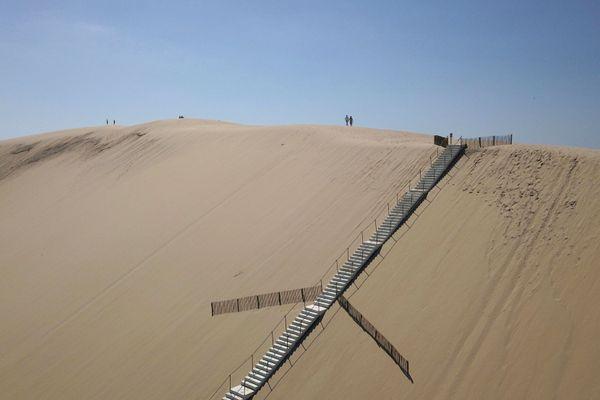 Des visiteurs atteignent le sommet de la Dune du Pilat, le 28 mai 2020, après sa réouverture à la fin du confinement.
