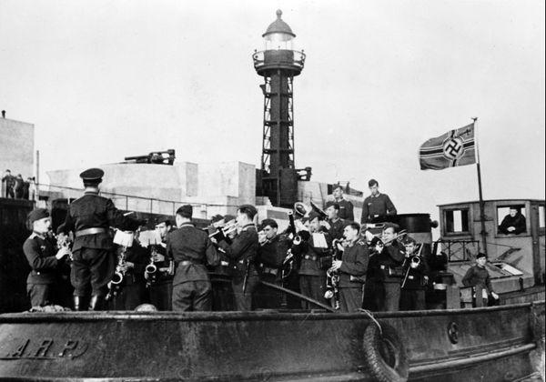 """Image de propagande allemande publiée en octobre 1940 montrant des soldats allemands jouant de la musique sur un bateau, dans un port français de la Manche, pendant les préparatifs de l'Opération """"Seelöwe'""""."""