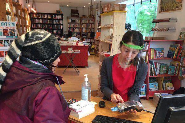 Protégé par sa visière, la libraire accueille une habituée à L'escampette