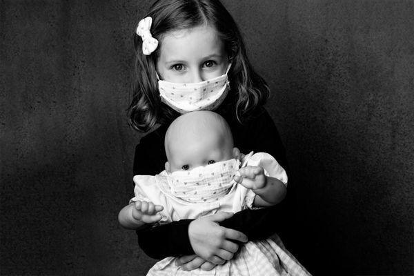 Une fillette pose masquée sous l'objectif de la photographe aixoise Sophie Bourgeix. Elle tient dans ses bras son poupon dont le visage est lui aussi partiellement couvert d'un masque.