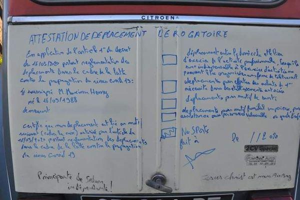 L'attestation de déplacement sur le coffre de la 2CV.