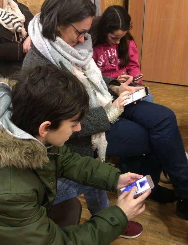 Mathéo, Laëtitia et Lilou sont sur leur portable en attendant le début de la conférence sur les dangers des réseaux sociaux.